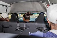 Der Polizist Themba Runeli (vorne rechts) fährt einen beschlagnahmten Minibus in Kapstadt, Südafrika. Die Fahrgäste werden an einem zentralen Standort herausgelassen, bevor das Taxi in ein Depot gefahren wird. Links der Fahrer, der eine nicht genehmigte Route benutzt hatte
