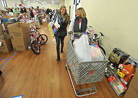 NWA Media/Michael Woods --12/17/2014-- w @NWAMICHAELW...Macy Bodishbaugh (left) and Margo Bodishbaugh help carry out a basket full of toys Wednesday morning to a family at the Salvation Army building in Springdale.  Several volunteers helped distribute toys and food to local families for the holidays during the Salvations Army's annual event..