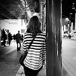 A woman in a stiped shirt, smoking, leaning on a lamp post on Granville Street at night.