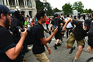 Washington, DC - August 12, 2018: A photographer is pushed after a  protester shouted for him to move as they marched near the White House in Washington, D.C. to oppose the Unite the Right rally in Lafayette Park August 12, 2018.  (Photo by Don Baxter/Media Images International)