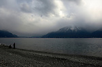 People on a stoney beach with a background of stormy clouds on lake Léman, Vevay, close to Montreux,Lausanne, Switzerland.