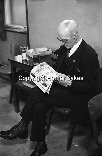 An old age pensioner wearing his suit drinking alone and reading a newspaper, Sunday morning at Byker &amp; St.Peters Working Men's Social Club Newcastle upon Tyne, Tyne and Wear northern England 1973. Typically he is wearing his &quot;Sunday best&quot; clothes.<br /> <br /> Mr William Surley. The badge that you see on his lapel is his committee badge, he dressed like that all the time. A remarkable man who went to the Somme aged 15, got sent home and went back when he reached 16. Info his grandson Ken Surley.