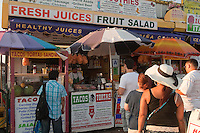 People line up by a food vendor on Coney Island boardwalk in New York city borough of Brooklyn, Sunday July 31, 2011. Built in 1923 and officially named The Riegelmann Boardwalk, Coney Island Boardwalk is located along the southern shore of the Coney Island peninsula adjacent to the Atlantic Ocean.