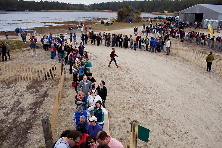People wait in line for a bog tour during the AD Makepeace Company's 10th Annual Cranberry Harvest Celebration in Wareham, Massachusetts, USA. AD Makepeace is the world's largest producer of cranberries. These cranberries, wet harvested with varied colors, are destined for processing into juice, flavoring, canned goods and other processed foods.