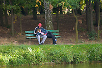 Couple talking on bench in the city park. Rawa Mazowiecka Central Poland