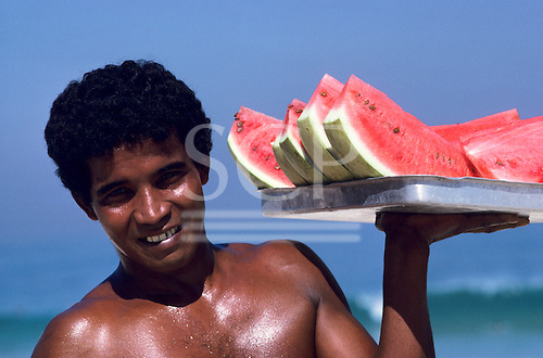 Rio de Janeiro, Brazil. Smiling young man carrying a tray of succulent watermelon slices for sale on the beach.