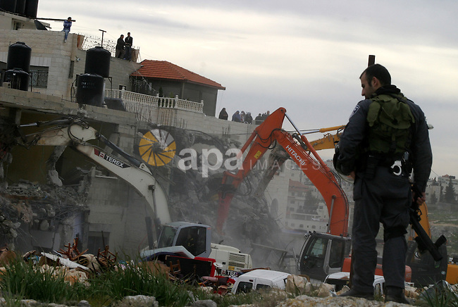 An Israeli security officer stands guard as bulldozers destroy a Palestinian house in the Arab east Jerusalem neighborhood of Beit Hanina on February 5, 2013. Palestinian homes built without a construction permit are often demolished by order of the Jerusalem municipality. Photo by Mahfouz Abu Turk