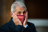 Anthony Fauci, director of the National Institute of Allergy and Infectious Diseases, adjusts a Washington Nationals protective mask while arriving to a Senate Health, Education, Labor and Pensions Committee hearing in Washington, D.C., U.S., on Tuesday, June 30, 2020. Top federal health officials are expected to discuss efforts to get back to work and school during the coronavirus pandemic. <br /> Credit: Al Drago / Pool via CNP /MediaPunch