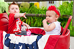 Cole Lombardo (left) of Rockville Center points out marchers to his cousin Mia Drogan (right) of Merrick, in red white and blue wagon, while watching the Merrick Memorial Day Parade on Monday, May 28, 2012, on Long Island, New York, USA. America's war heroes are honored on this National Holiday.