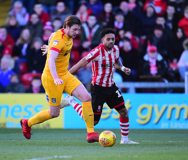 Lincoln City's Bruno Andrade under pressure from Northampton Town's Ash Taylor<br /> <br /> Photographer Andrew Vaughan/CameraSport<br /> <br /> The EFL Sky Bet League Two - Lincoln City v Northampton Town - Saturday 9th February 2019 - Sincil Bank - Lincoln<br /> <br /> World Copyright © 2019 CameraSport. All rights reserved. 43 Linden Ave. Countesthorpe. Leicester. England. LE8 5PG - Tel: +44 (0) 116 277 4147 - admin@camerasport.com - www.camerasport.com