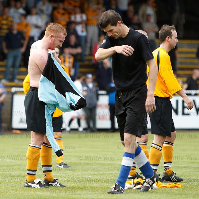 Defender Peter Jordan pulls on the goalie's top as keeper Paul McCann trudges off dejected