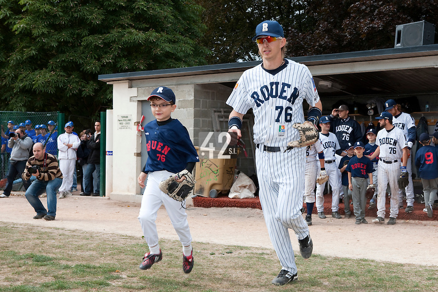 03 october 2009: Young fan and baseball player Victor Rolland runs along Luc Piquet during players introduction prior to game 1 of the 2009 French Elite Finals won 6-5 by Rouen over Savigny in the 11th inning, at Stade Pierre Rolland stadium in Rouen, France.