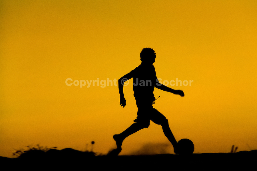 A young boy plays football during the sunset on the beach in Uruau, a small fishing community in the northeastern Brazil, 21 March 2004.