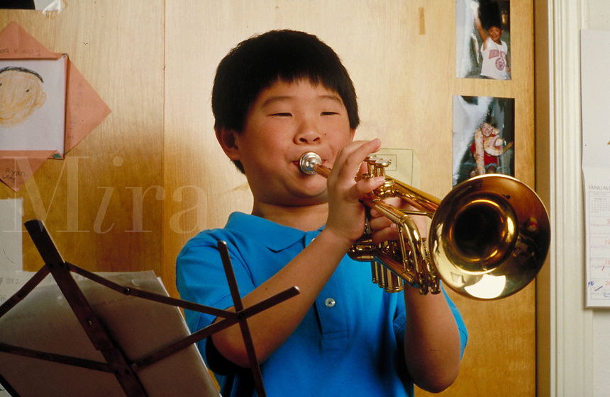 CHINESE-AMERICAN BOY PRACTISING HIS TRUMPET. BOY PLAYING TRUMPET. SAN FRANCISCO CALIFORNIA USA.