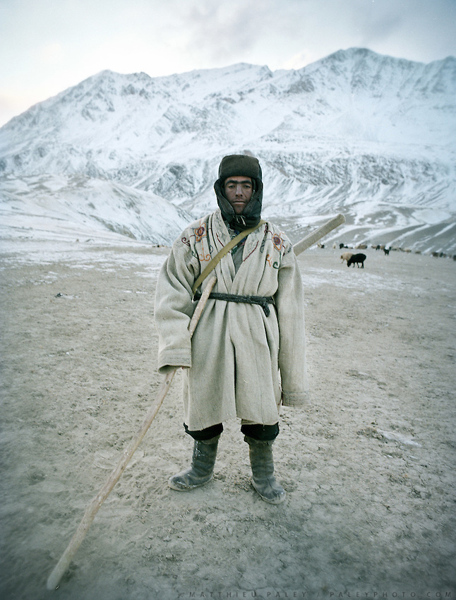 "Mohammad, Wakhi shepherd wearing traditional ""Chapan""..Wakhi winter shepherds known as ""Shpunds"" in their settlement of Kher Metek, on the edge of the Little Pamir. They often look over Kyrgyz sheep and yak herds for payment in animals. .Winter expedition through the Wakhan Corridor and into the Afghan Pamir mountains, to document the life of the Afghan Kyrgyz tribe. January/February 2008. Afghanistan"