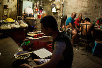 "People eat at a small unnamed outdoor noodle cafe at the bottom of Shibati, or 18 Steps, in central Chongqing. The cook, Tong Su Chun, has been cooking at the spot, which is run by his nephew, for about 20 years. The neighborhood is slated for redevelopment, and all residents, including this shop, must leave the area by October 2014. Tong Su Chun said he didn't know what he would do after the restaurant closes. ""I'll take a break,"" he said, ""and then find something new."" The restaurant typically serves a couple hundred people in a night, most spending about 15 RMB."