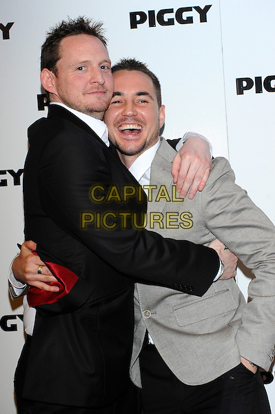 "Keiron Hawkes & Martin Compston.The Premiere of ""Piggy"" held at the Odeon, Covent Garden, London, England..May 1st, 2012.half length white shirt grey gray suit stubble facial hair black hug embrace .CAP/CJ.©Chris Joseph/Capital Pictures."