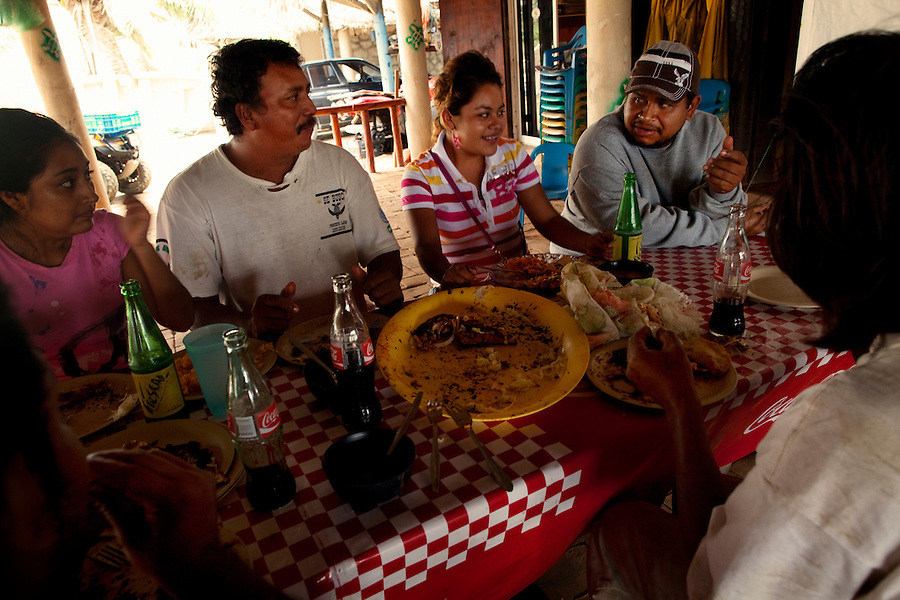 Barra Vieja, Mexico, February 18, 2012 - Members and volunteers of Campamento Tortuguera, from left, Maria Luisa Ramos Nino, Sabino Mendoza Guatemala, Sofia Valderrabano Perez, Camp Director Victor Jesus Verdejo Ramirez, and Juan Carlos Gonzales Segovia, nicknamed 'Chango León', enjoy a lunch together after releasing around 45 Leatherback sea turtles that morning.