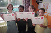 Multiracial group of primary school children holding up achievement certificates following Drug Abuse Resistance Education training,