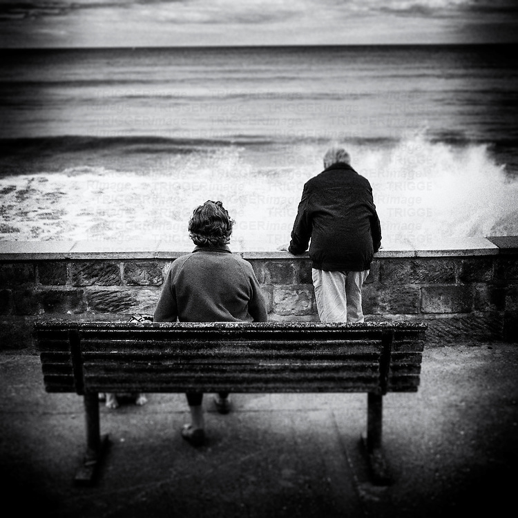 Elderly couple (woman seated on bench) and man (looking over wall) watch the high waves crashing in.  Dog also present, just visable under bench.