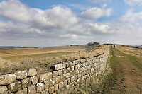 Section of Hadrian's Wall between Steel Rigg Car Park and Windshields wall, Northumberland, England. Hadrian's Wall was built 73 miles across Britannia, now England, 122-128 AD, under the reign of Emperor Hadrian, ruled 117-138, to mark the Northern extent of the Roman Empire and guard against barbarian attacks from the Picts to the North. The wall was fortified with milecastles with 2 turrets in between, and a fort about every 5 Roman miles. This section of the Wall is in the Northumberland National Park, managed by the National Trust, and the Hadrian's Wall Path, an 84-mile coast to coast long distance footpath, runs alongside it, together with a section of the Pennine Way. Picture by Manuel Cohen