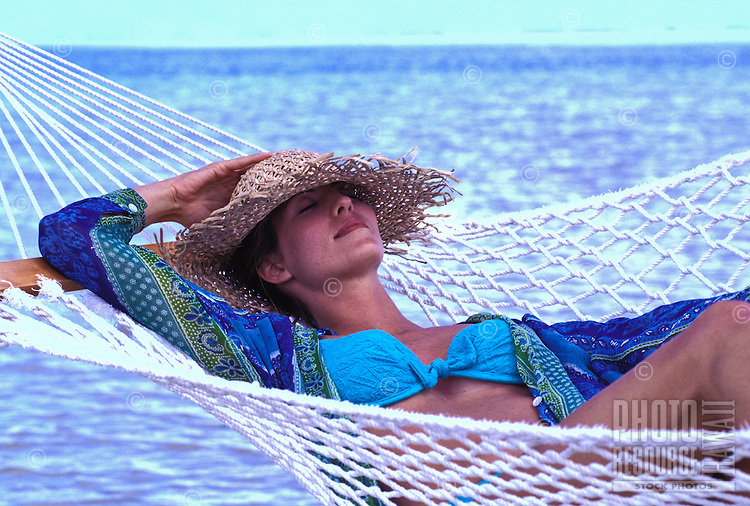 Woman wearing a straw hat relaxes in a hammock near the sea.