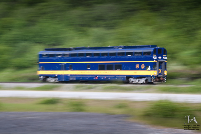 Passenger train in Alaska running by Turnagain Arm, doubledecker Chugach Explorer, caught with motion blur by panning