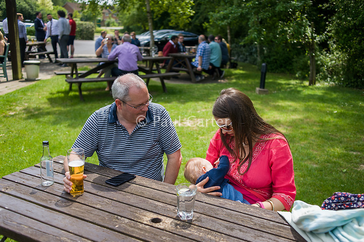 A mother breastfeeding her baby in a pub garden. Her husband is sitting beside her drinking a pint of beer.<br /> <br /> Hampshire, England, UK<br /> 19/06/2013<br /> <br /> &copy; Paul Carter / wdiip.co.uk