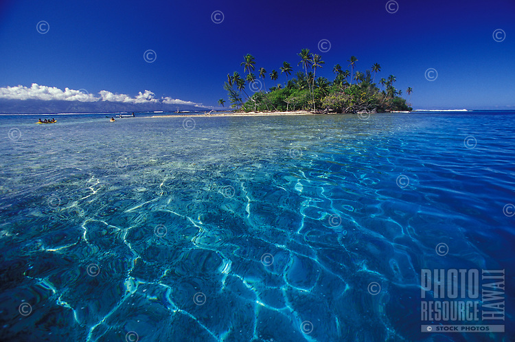 Crystal clear lagoon waters of Moorea lagoon with motu island and kayakers in background, Tahiti, French Polynesia