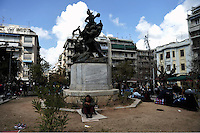 Pictured: Migrants camp around a sculpture Friday 26 February 2016<br /> Re: Hundreds of refugees have temporarily camped at Victoria Square in central Athens, Greece.