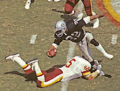 Washington Redskins defensive end Dave Butz (65) holds on to Los Angeles Raiders running back Marcus Allen (32) during their game at RFK Stadium in Washington, D.C. on September 14, 1986.  The Redskins won the game 10 - 6.<br /> Credit: Arnold Sachs / CNP