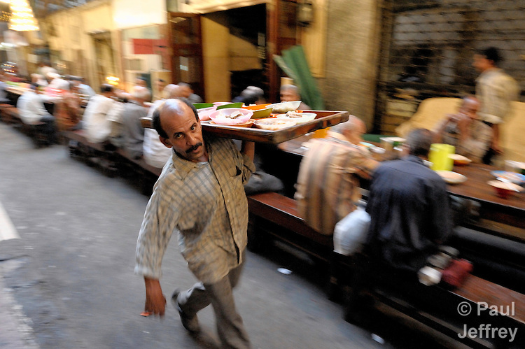 Muslims throughout the world break their daily fast during the holy month of Ramadan by sharing the iftar, the evening meal celebrated just after sunset, often in community. The iftar also demonstrates hospitality, and faithful Muslims often provide the meal at no cost as an act of charity. In this photo, an iftar is celebrated on a narrow street in the Egyptian city of Cairo.