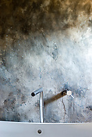 A stainless steel tap strikes a contemporary contrast against the rustic rough plaster wall of the bathroom