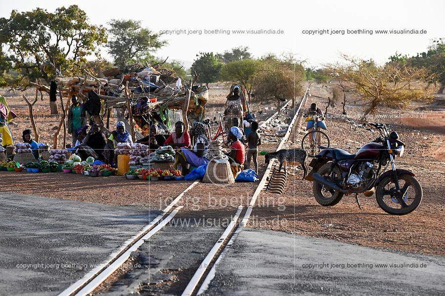 BURKINA FASO, Kaya, abandoned railway line to the Manganese ore mines in Tambao, built during Thomas Sankara time, people selling vegetable at road rail crossing / von Sankara gebaute Eisenbahnlinie zu den Mangan Lagerstätten in Tambao