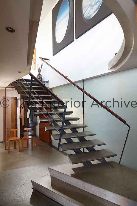 An elegant, contemporary staircase seems to defy gravity in a spacious entrance hall.