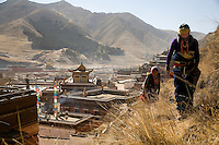 Tibetan Buddhist pilgrims walk along trails above the Labrang Monastery in Xiahe, Gansu Province, China.  The monastery is one of the most important pilgrimage sites outside Tibet and each year thousands of pilgrims, mostly nomadic Tibetans, travel to the area for during the Lunar New Year period.
