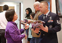 NWA Democrat-Gazette/DAVID GOTTSCHALK  Chung Tan (from left), with the Fayetteville Chamber of Commerce, speaks Friday, January 11, 2019, Tech. Sgt. Brad Cargill, with the Air National Guard, following the unveiling of the new workforce textbook A Calling at a press conference at the commerce office in Fayetteville. The book has 28 local employers describing the career pathways in their organization. The textbook will be distributed to every middle and high school student attending Fayetteville Public Schools. The textbook will be used by the teachers during their CTE classes.