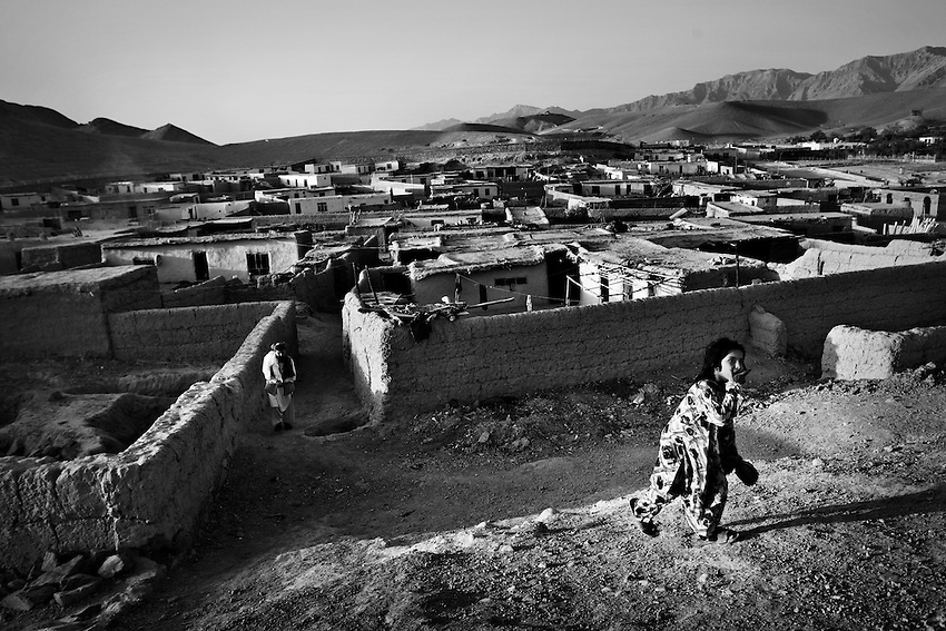 An Afghan girl walks on a ridge near the village of Puli Charkhi, which has been built up by returnees, Puli Charkhi, Afghanistan, Oct 7, 2009.
