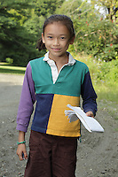 Hortonia, VT, USA - August 21, 2011: Young girl in countryside lane with her nature journal notebook and pen