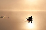 Sunrise in fog Lake Cassidy with fishermen in small fishing boat heading out to fish