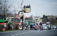 breakaway group riding through a farmers protest <br /> <br /> 99th Ronde van Vlaanderen 2015