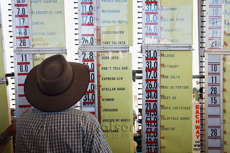 A bookie checks the betting odds for races at the Birdsville Cup horse races.  Every September thousands of horse racing enthusiasts arrive in the outback town on the edge of the Simpson Desert for the famous outback racing carnival.  Birdsville, Queensland, AUSTRALIA.
