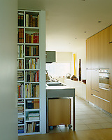 Bookshelves flank the entrance to this open-plan modern kitchen
