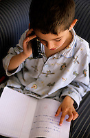 Young boy discussing his homework with a friend on the phone.