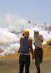 Palestinian and foreign protestors run away from  tear gas threw by Israeli soldiers during a demonstration against Israel's controversial separation barrier in the West Bank village of Bilin near Ramallah on July 17, 2009. Photo by Nedal Shtieh
