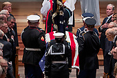 President Donald Trump, top left, and former President George Bush, top right, watch as the flag-draped casket of former President George H.W. Bush is carried by a military honor guard during a State Funeral at the National Cathedral, Wednesday, Dec. 5, 2018,  in Washington. <br /> Credit: Andrew Harnik / Pool via CNP