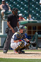Charlotte Knights catcher Zack Collins (8) gives signs to his pitcher as home plate umpire Erich Bacchus looks on during the game against the Durham Bulls at BB&T BallPark on May 27, 2019 in Charlotte, North Carolina. The Bulls defeated the Knights 10-0. (Brian Westerholt/Four Seam Images)