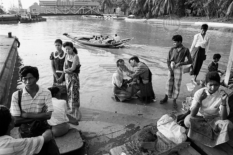 Passengers wait for boats on the Rangoon River.
