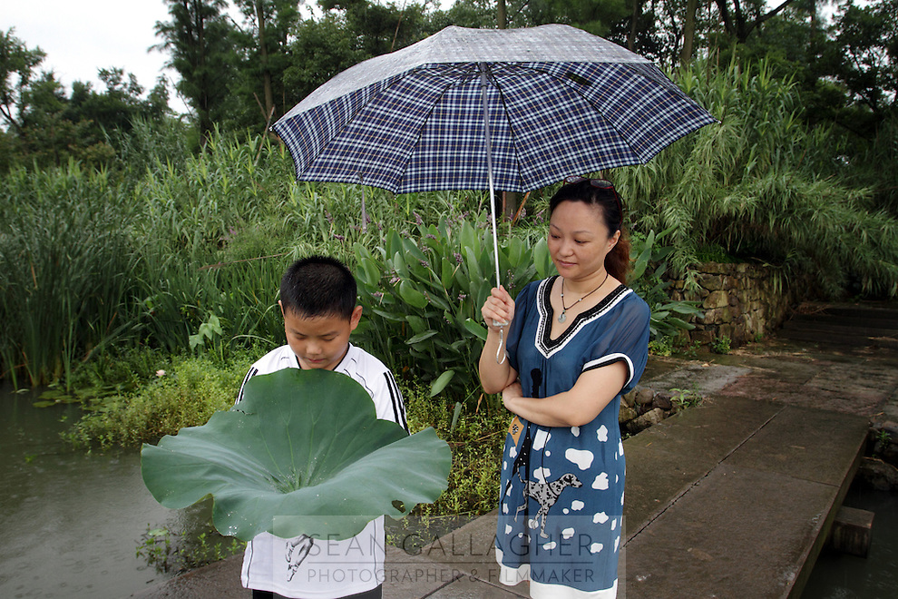 A mother and her child attempt to catch rain in a leaf at The Xixi wetlands which lie in the west of the city of Hangzhou. This is China's 'first national wetland park,' dubbed as such to act as a role model to all other wetlands in China and to supposedly show how to effectively manage and restore wetlands, notably urban wetlands. Zhejiang Province. China. 2010