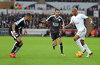 Andre Ayew of Swansea (R) against (L-R) Danny Simpson and Riyad Mahrez of Leicester City during the Barclays Premier League match between Swansea City and Leicester City at the Liberty Stadium, Swansea on December 05 2015